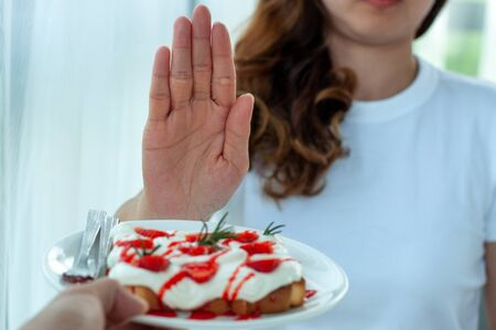 Young woman uses the hand to push the plate of pastry, refusing to eat flour and sugar, intended to lose weight.