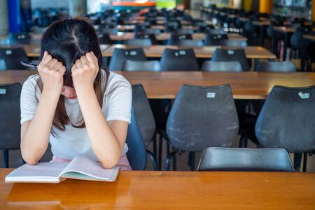 Upset girl  sitting alone at school table Feeling lonely and think too much alone.