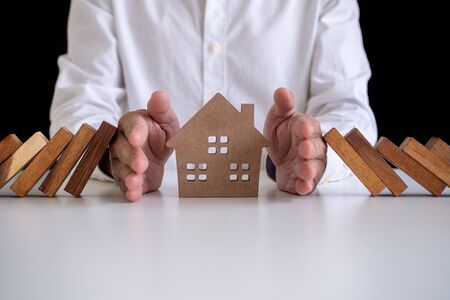 Small house covered by hands Insurance concept Residential house