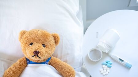 The teddy bear is sick in the bed next to him. There is medication, thermometer waiting to be treated. 免版税图像