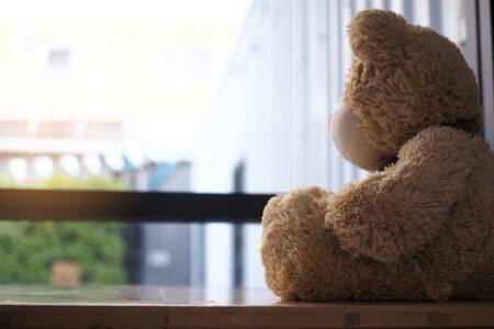 major depressive disorder mdd concept. Grief of children. Teddy bear sitting looking at the house window alone. Looks like someone who is sad, disappointed, depressed