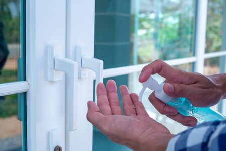 Man's hand pressing the gel to wash hands to kill germs before going in and out or catching doors.