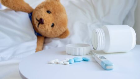 Brown teddy bear is sick in bed depression beside, there was a medicine placed on the table.