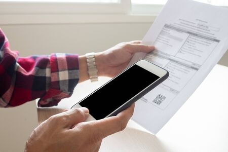 Hand uses smartphone scan QR code or barcode to pay monthly phone bills.