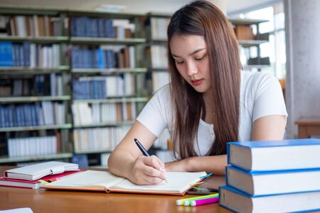 Asian female student sitting at a desk and writing in a notebook. Young female students do homework in the library Standard-Bild