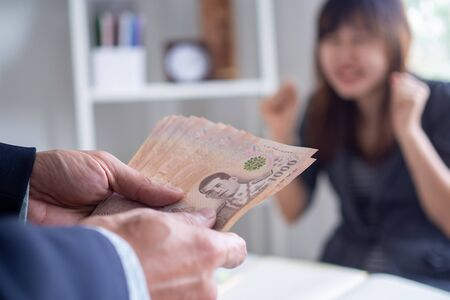 Hand of thai executives or bosses hold Thai baht in salary or bonuses to deliver to employees