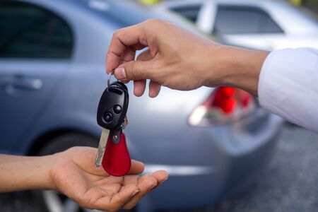 Businessman handing over gives the car key for rental or sell to the customer on car background. salesman receiving money and giving car`s key to customer after sign agreement contract.