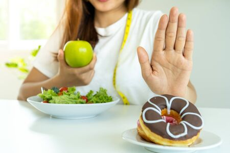 Diet concept. Healthy women use hands to reject unhealthy foods such as donuts or desserts. Slim women choose healthy foods and high vitamins, such as apples and vegetable salads. Standard-Bild