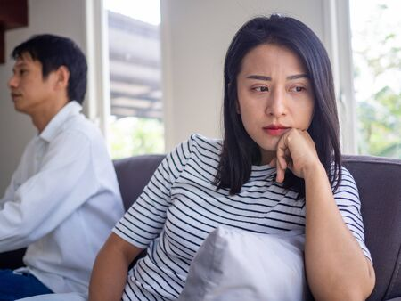 Beautiful Asian women think or upset about love problems want to divorce. The wife is stressed and sad after an argument with her husband. Problems family relationships have to say goodbye and end Imagens