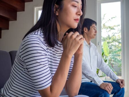 Depressed young wife feels resentful and sad. After an argument with a stubborn husband sitting on the sofa unhappy young wives bored with bad relationships, bored with marriage problems