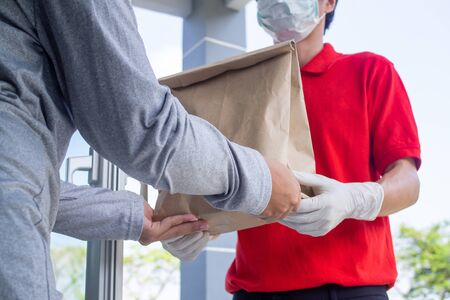 One woman ordered food online to eat at home. The person orders products or food online, receives parcels from delivery man That put a mask on the door of the house. Stockfoto