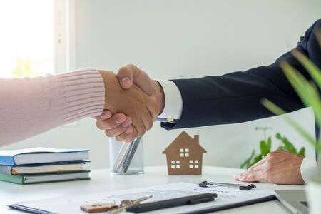 sales agents and customers shaking hands after signing a contract to buy a new house or apartment. mortgage,landlord concept