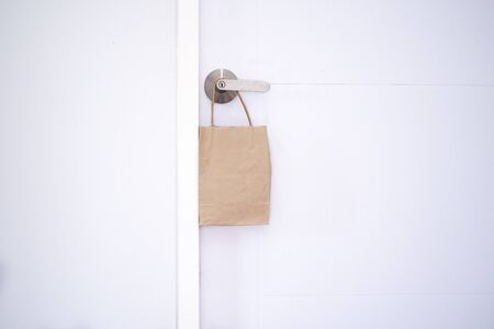 Online shopping and express delivery concept. Cardboard bags for food. Food bags hung in front of the house door. Transporting food and goods. fast and free delivery.  Internment