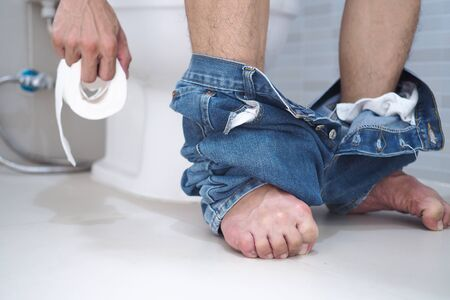 man sitting in the toilet in hand was a toilet paper roll. Spastic on the feet due to severe stomach pain. The cause may be diarrhea.
