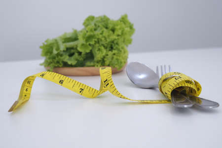 Lettuce and measuring tape wrapped around a spoon and fork. Healthy Food and diet concept 版權商用圖片