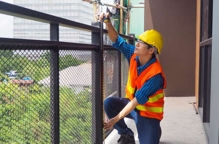 The inspector or engineer is inspecting and measuring the size of the building terrace.