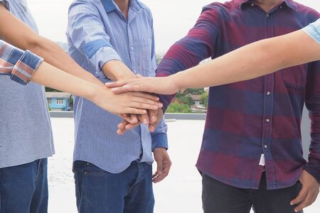 Young people hold hands Colleagues show their unity and teamwork.