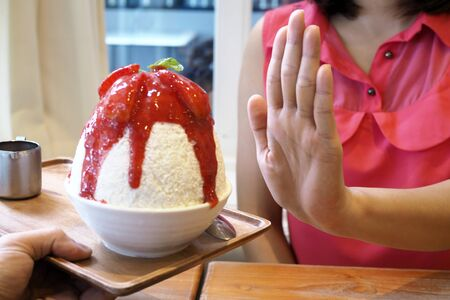 Women push the ice cream cup. Refused to eat all kinds of sweets. Avoid sugar and sweets for good health. diet concept Standard-Bild