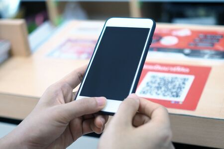 Hands use the phone to scan the QR code to receive discounts on purchases in the department store.