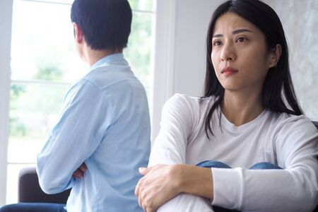 An Asian couple is stressed and upset after an argument.