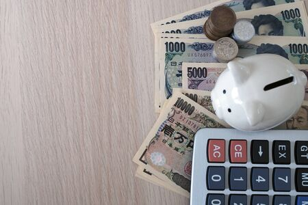 Piggy bank and calculator Placed with Japanese Yen banknotes and Japanese Yen coins for money concept background