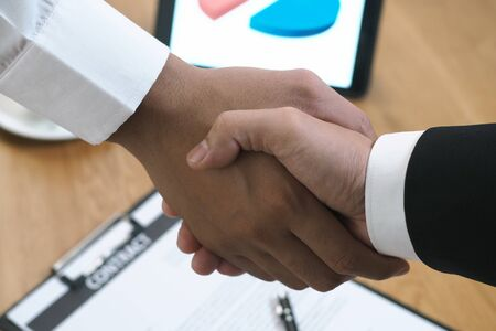Two businessmen join hands to sign a contract after negotiating an investment and profit agreement.