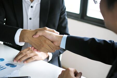 Businessmen handshake to invest and share profits in building and residential projects. Have a contract document that has legal effect