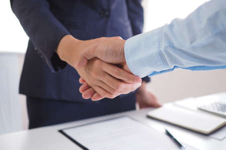 Two businessmen shake hands after negotiating the agreement and signing the contract. Banco de Imagens