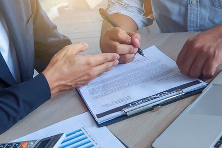 Businessmen show gestures inviting them to sign a business contract. The law is effective. Signing the contract concept. Stock Photo