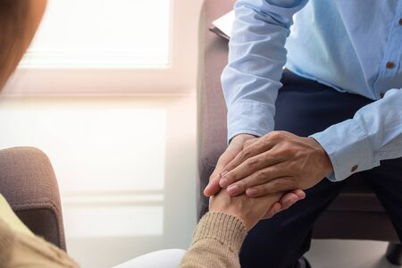 Psychiatrist is touching hands to comfort women with depression or female patients have been sexually abused. Treatment , Listening and consulting concepts. Encouragement and consolation