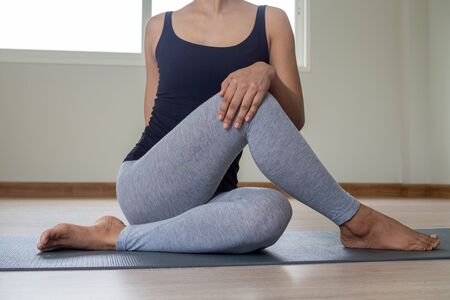Beautiful and healthy women exercising and doing seated twist yoga in private rooms at home.