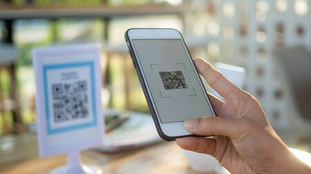 Using mobile phones to pay scanning promotional discounts in restaurants. Foto de archivo