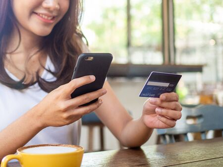 Female sitting in a coffee shop, transferring money, shopping by credit card through the app, via notebook Convenient and fast choice.