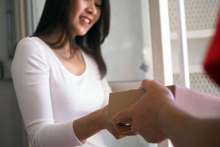 Women's hands signed to receive packets from online purchases The young man sent the smartphone and box
