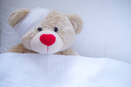 Creamy teddy bear injured in a wound after an accident Foto de archivo