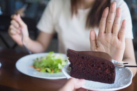 The girl is pushing the chocolate cake out. And choose to eat salad vegetables placed in front. The goal is to lose weight and eat healthy food.