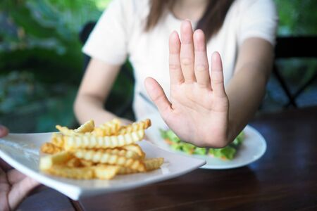 Women refuse to eat fried or french fries for weight loss and good health. Standard-Bild