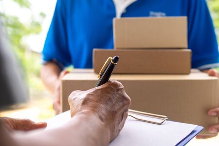 The landlord's hand is signing to receive the parcel sent by delivery man. Banco de Imagens
