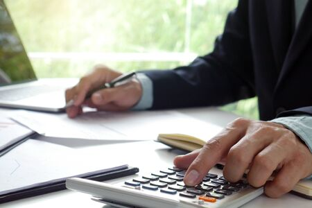 Men use the calculator and take notes with calculations about the expenses at the office. Prepare to submit annual tax