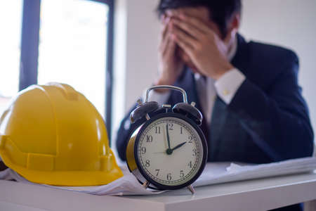 Image Clock focus. Background: Business people are serious and stressed about working in the office until late the lunch break due to pressure and encounter problems in the job.
