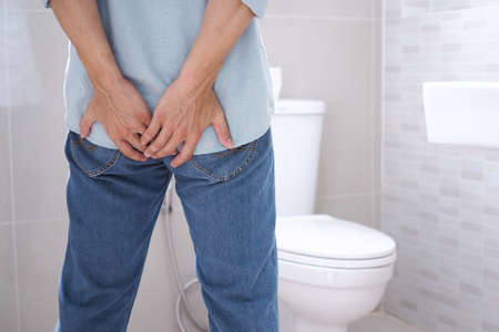 Asian man suffers from diarrhea near a toilet bowl have abdominal stomachache ,constipation in bathroom sick people hand from the belly diarrhea stomach health problem.