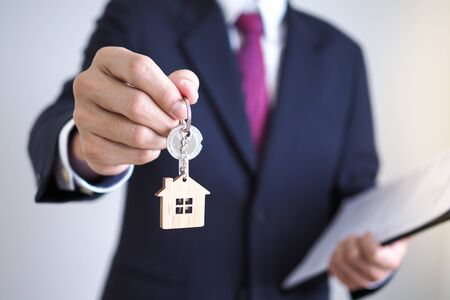 Home sales agents are giving home keys to new homeowners. Landlords and house keys concept Standard-Bild