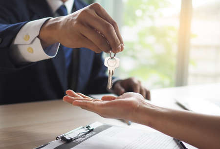 House salesmen are sending keys to new homeowners. Buying, selling, renting, changing homes