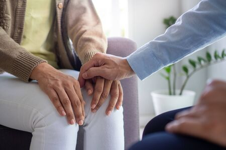 The hands of a psychiatrist hold the patient's hand to encourage and encourage recovery from depression. Stockfoto