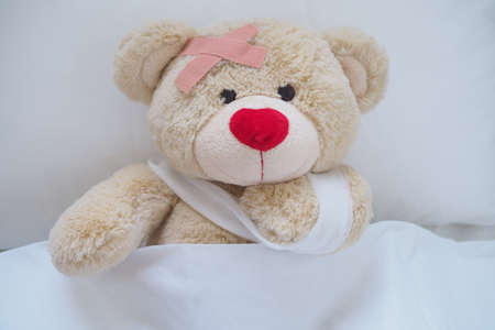 Teddy bear with a wound dress, wound and broken hands. Sleeping in bed. Sickness of children