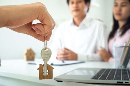 The male salesman is giving the house keys to a couple, husband and wife, after talking about the sale - home mortgage. The sales home mortgage concept