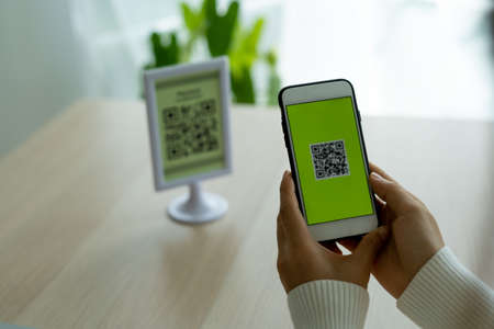 The woman's hand is using the phone to scan the qr code to select the food menu. Scan to receive discounts or pay for food and to use to transfer money online without cash in restaurant or cafe.