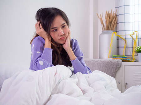 Unhappy woman in a bedroom. A beautiful Asian woman was sitting in bed with a bored gesture, thinking what to do during the day feeling lonely. Foto de archivo