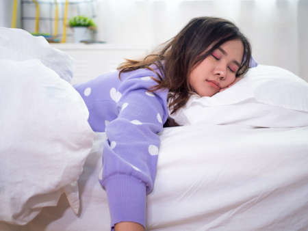 A beautiful Asian woman sleeping in bed. Woman are lazy awake and lethargic. Sleep and rest during the holidays.