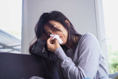 Asian women are sick with runny noses and colds. Ill young woman covered with blanket and sneeze. Sick woman concept
